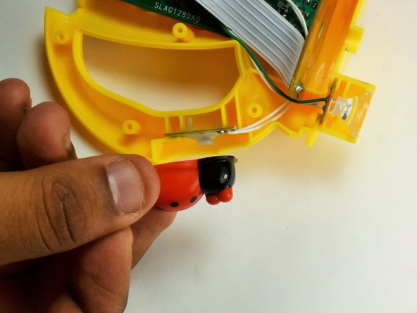 Locate the ladybug button on the handle of the opened flashlight and remove it from its slot.