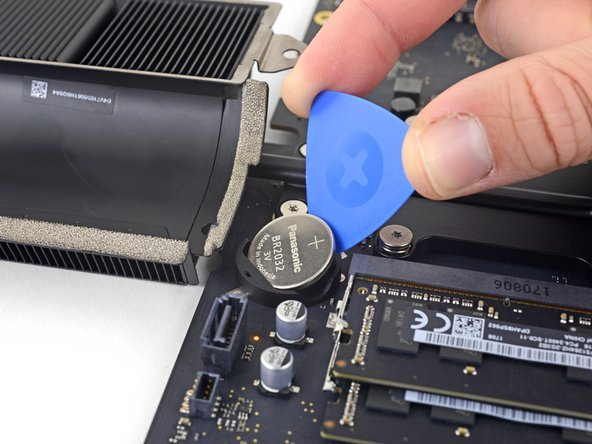 On the side between the two plastic nubs (opposite the spring contact), gently slide an opening pick in between the battery socket wall and the battery.