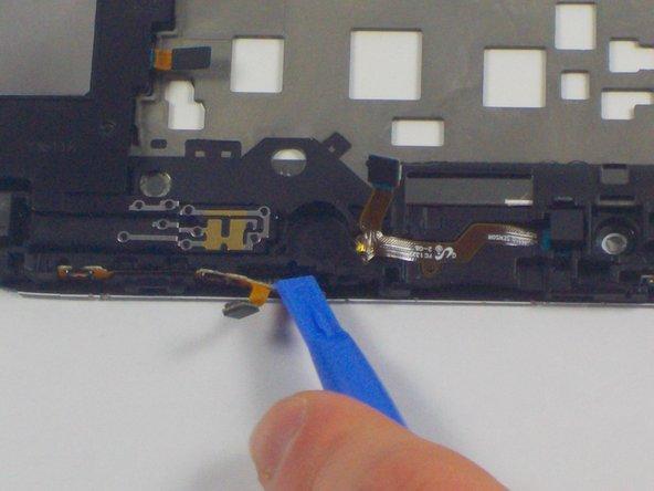 Setze das Plastiköffnungswerkzeug zwischen die Lautstärketasten und dem inneren Rahmen. Schiebe es dann vorsichtig nach links, dabei lösen sich die Lautstärketasten vom Rahmen.