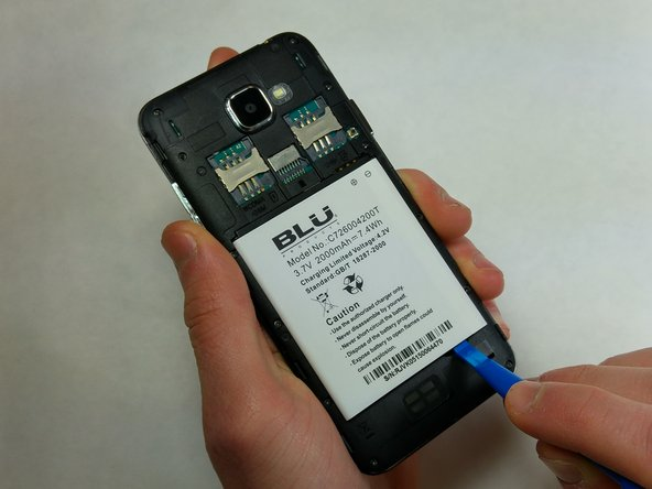 Pry the battery out from the back of the phone using the plastic opening tool.