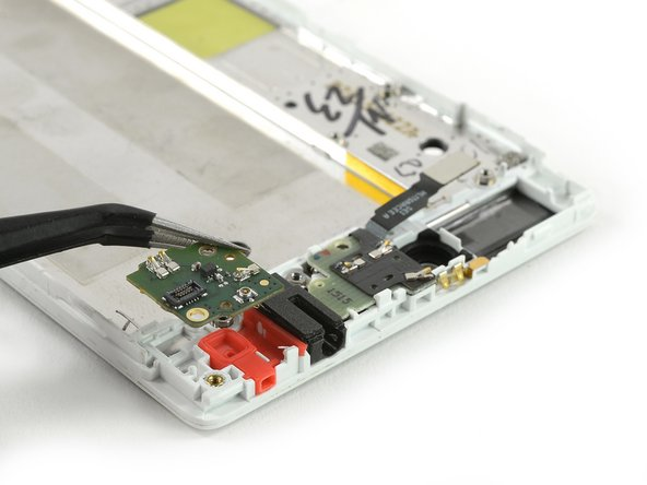 Use a tweezer to remove the first daughter board which was connected to the headphone jack.