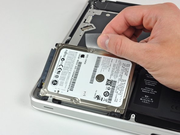 Image 1/1: Lift the hard drive by its pull tab and pull it out of the chassis, minding the cable attaching it to the computer.