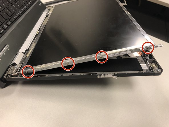Use a Phillips #00 screwdriver to unscrew all four 0.8 mm screws from the left side of the display frame. Repeat for the right side.