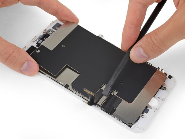 Lift the LCD shield plate while pressing down on the flex cable it surrounds.