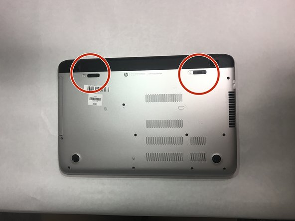 Flip over your HP Pavilion to the backside, so you see the battery release and battery unlock slide mechanisms.
