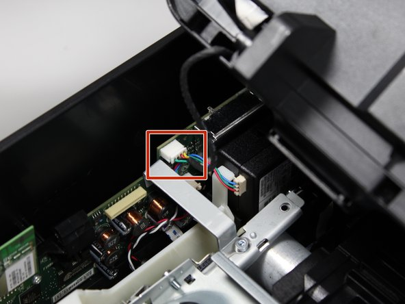 Remove the cables that connect the cartridge access door to the motherboard by pinching the front of the cable box with two fingers and pulling it away from the motherboard.