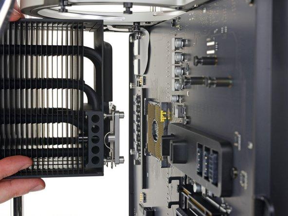 Sin una guía de reemplazo de la CPU a la que acudir, llamamos a un audible y desenroscamos el soporte del disipador de calor de la parte trasera del soporte de liberación de la placa lógica y de la CPU.