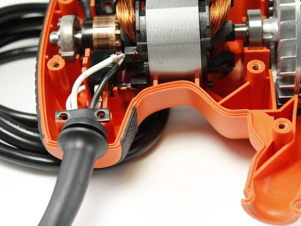 Use the bit driver with the JIS - J1 bit to remove the two 12.5 mm phillips screws holding the cord clamp to the chassis.
