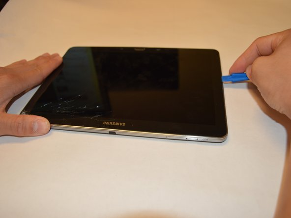 Image 1/2: Insert a plastic opening tool into the crevice between the screen and the side of the tablet.