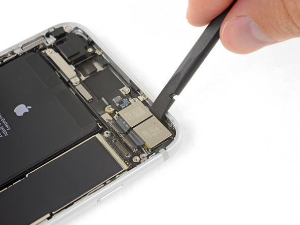 Use the flat end of a spudger to pry up the rear-facing camera assembly from the top edge of the iPhone.