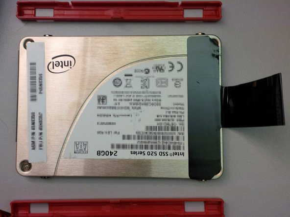 Remove the plastic rails from the old drive and place them on the new drive.