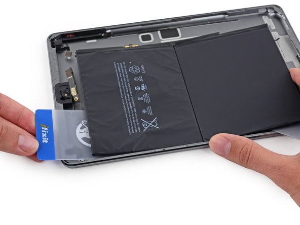 Press the card in further, breaking as much of the adhesive holding in the battery as you can.
