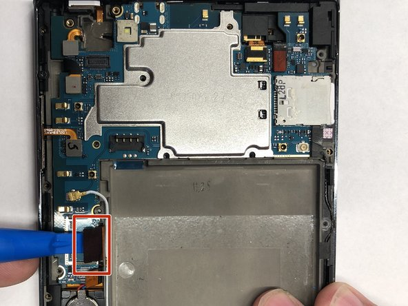 Carefully use the plastic opening tool to pry the ribbon cable below the volume buttons on the left side of the phone.