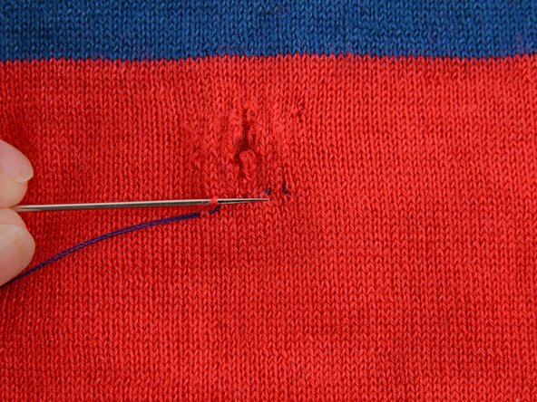 Turn the needle around and take a stitch going the opposite direction (towards where you started) just above your last row of stitches.