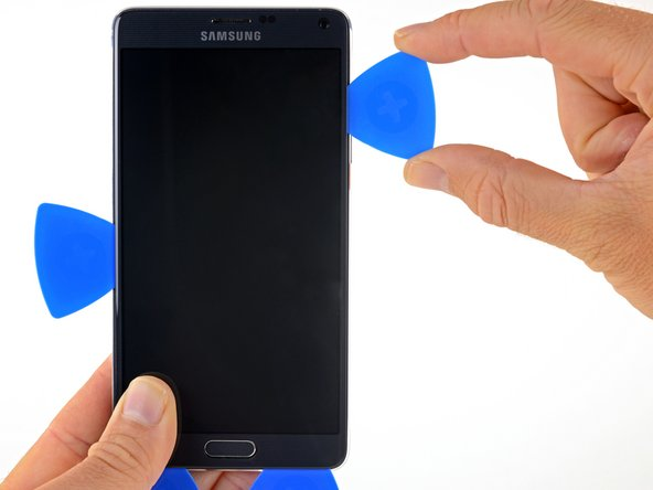 Slide the opening pick along the right edge of the display to separate the adhesive underneath.