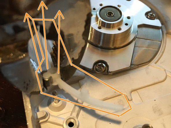 "Use a pair of pliers to remove the brass/rubber standoff (circled in red in the first picture) and the plastic bar (""circled"" in orange in the second picture) from the aluminum drive body. Pull hard and pull up."