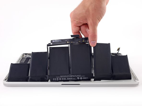 Image 1/2: Before installing your new battery, remove all the old adhesive from the MacBook Pro's case.