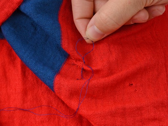 Slowly pull the needle through the fabric, creating a loop.