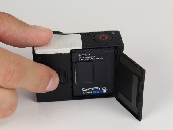 Pull back on the tab on the back of GoPro to open the battery cover.