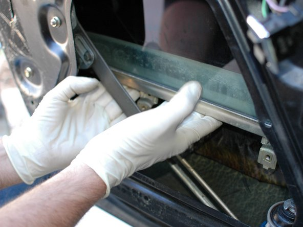 Separate the window regulator arm from the bottom rail on the glass and then slowly push the glass up in to the door.