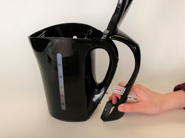 Using the three-winged screwdriver, unscrew two three-winged screws from the top of the handle cover and two three-winged screws from the bottom of the handle cover and separate the handle cover from the kettle