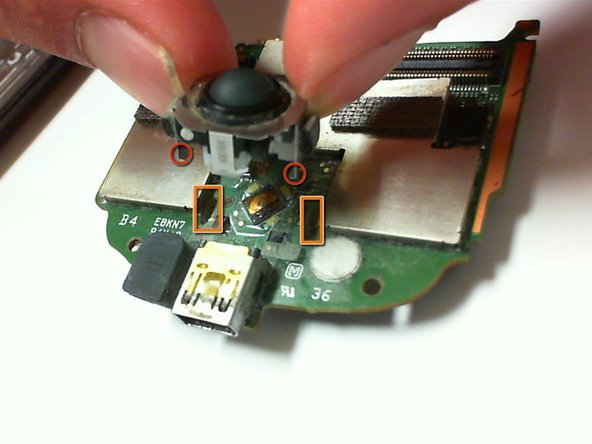 Use a precision flathead screwdriver to dislodge the prongs from the circuit board and push the prongs through the slots. The trackball should detach from the circuit board.