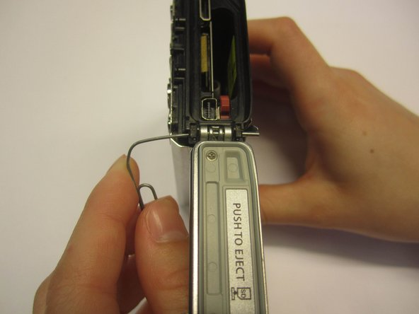 Using a paperclip, completely push out the metal bar that holds the side panel to the camera.