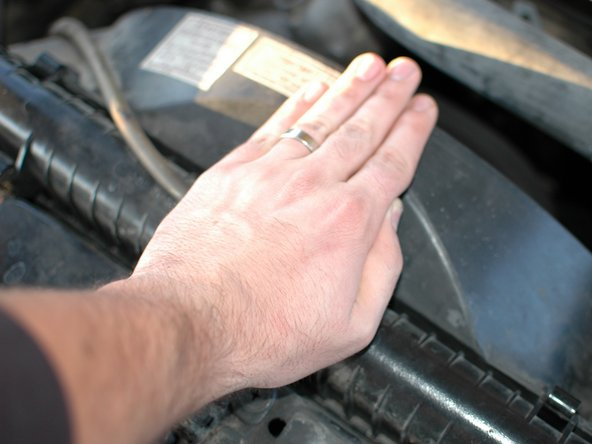 Once you have verified that the coolant is cool enough to proceed, use the palm of your hand to press down on the radiator cap and turn it counter clockwise.