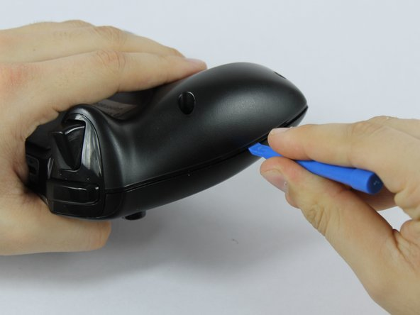 Use the plastic opening tool to pry the face of the controller away from the body.
