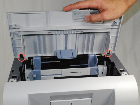 Remove the front panel by gently moving the holes on the panel from the pegs attached to the main printer body one at a time. Be sure to remove the entire front panel and not just the flap on the paper tray.