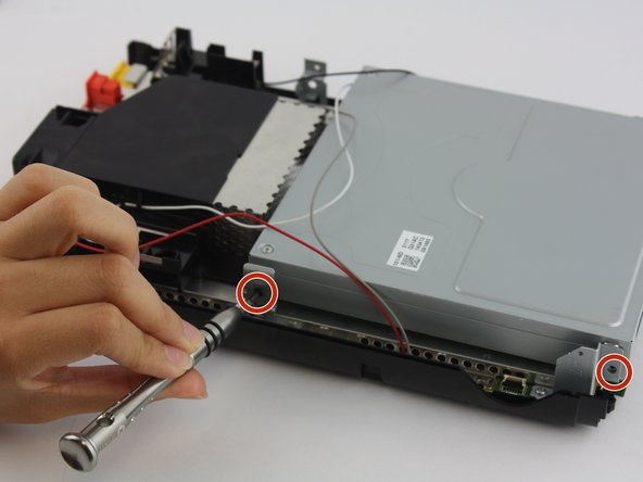 Using a Phillips #0 screwdriver, unscrew the four screws (two on each side) from the disc reader connecting it to the main console and remove disc reader.
