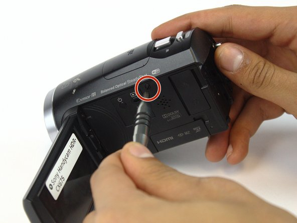 Turn the camera around and flip open the LCD screen to expose the side panel.