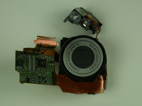 A ribbon cable prevents complete separation of the viewfinder and the lens assembly.