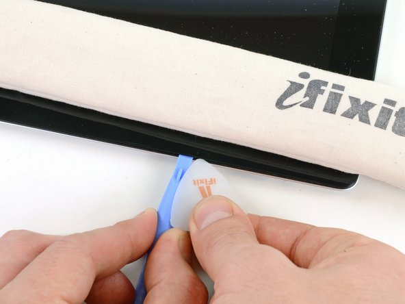 Lasse die Spitze des Plastic Opening Tools eingekeilt zwischen dem Frontglas und der Kunststoffeinfassung und führe ein Opening Pick in die Lücke,  direkt neben dem Plastic Opening Tool.