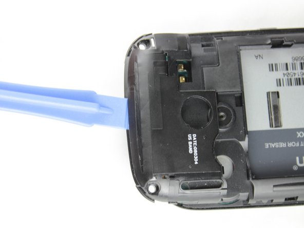 Use a plastic opening tool to remove the small panel on the top of the phone by prying underneath the black plastic around the camera.