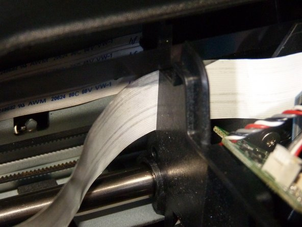 Image 3/3: Feed the ribbon cable in with the metallic strips/pins facing away from you
