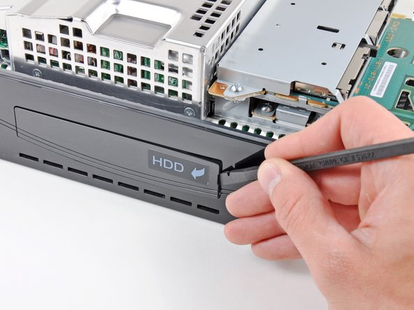 Image 1/2: Use the flat end of a spudger to pry the hard drive bay cover away from the lower case.