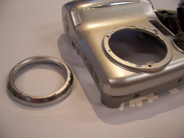 Use a Phillips screwdriver to unscrew the three screws that connect the outer lens rim to the front casing.