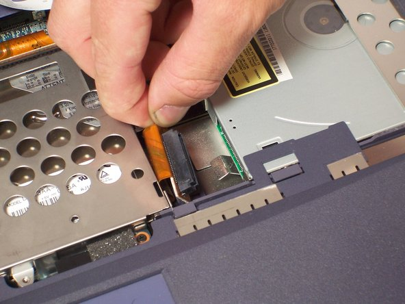 Carefully detach the harness from the CD/DVD drive. Use your fingers if possible, but if not carefully use a pair of tweezers to detach the harness.  Take care in not bending any of the pin connections.