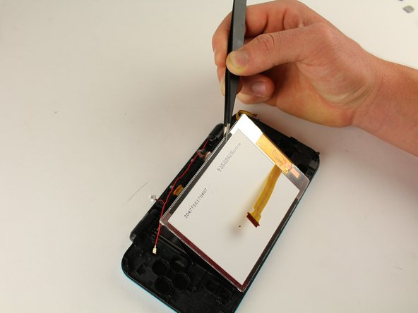 Using tweezers, pry up the touchscreen.