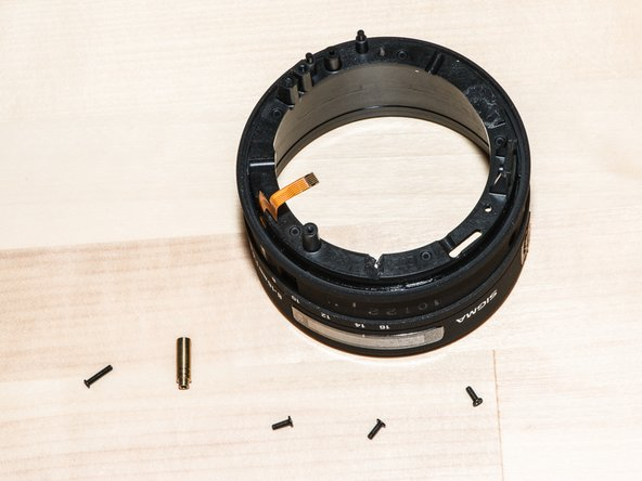 Remove the three screws around the outer ring. Lift off the zoom ring assembly. Don't snag the ribbon cables.