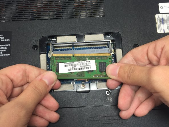 Remove the upper RAM chip from its socket by gently gripping the left and right edges with your fingers and pulling the chip towards your body until it slides completely free of the computer.