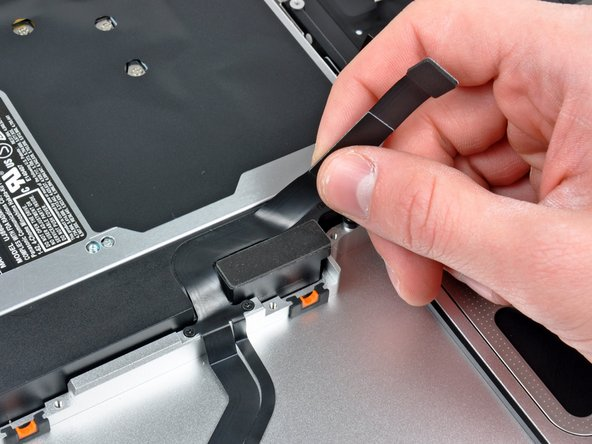 Carefully peel the hard drive cable off the adhesive securing it to the right speaker housing.