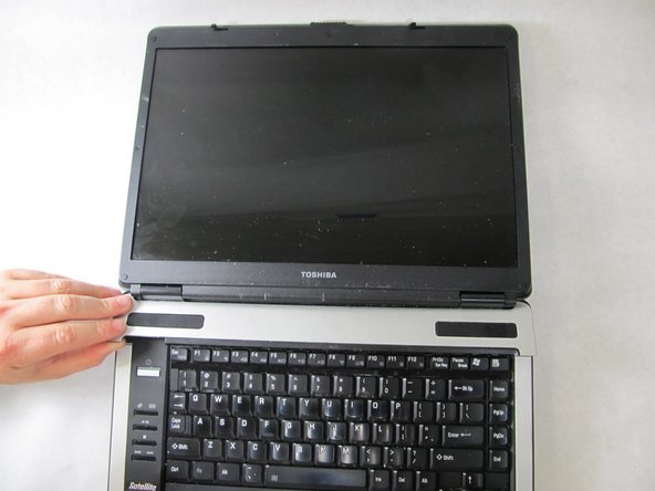 Remove the plastic piece from the body of the laptop so that you can now see the two speakers in each corner.