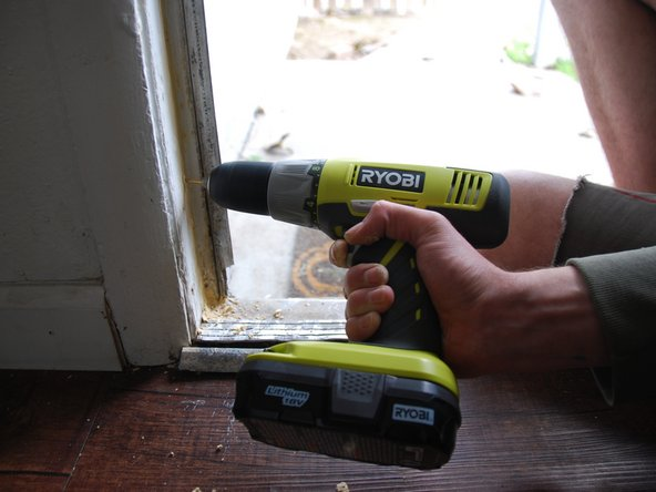Drill a pilot hole into the door frame.
