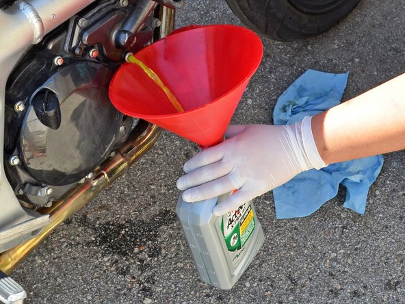 Finish removing the drain plug by hand and allow the coolant to drain into the container.