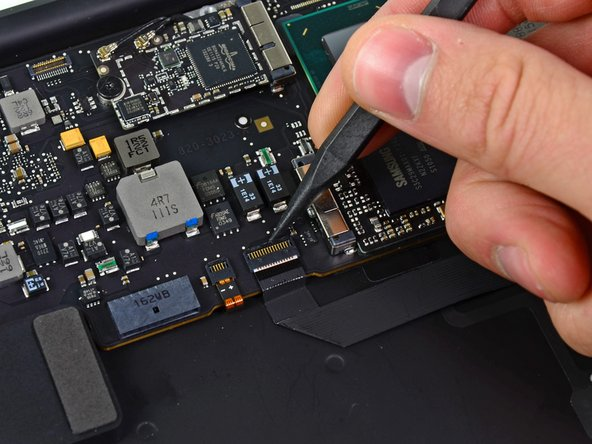 Use the tip of a spudger or your fingernail to flip up the retaining flap on the trackpad ribbon cable ZIF socket.