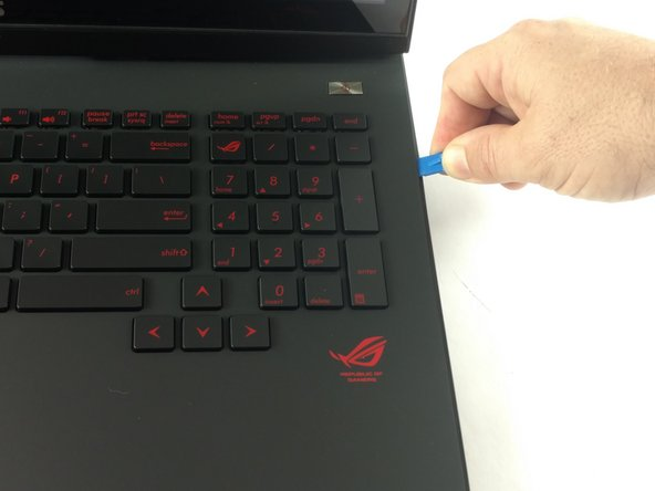 Use the plastic opening tool to pry the keyboard from the base of the laptop.