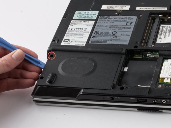 Image 1/3: Use the plastic flap to pull the hard drive out of its slot.