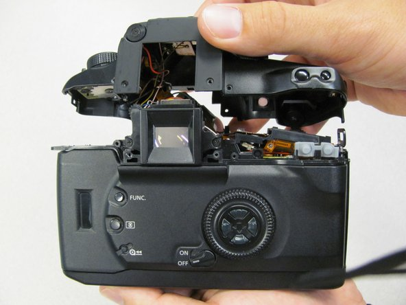 Separating the top panel too far or quickly can damage the ribbon cable and connecting wires that are still attached to the top panel of the camera.